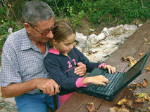 Grandfather with grandchildren and laptop Stock Photos