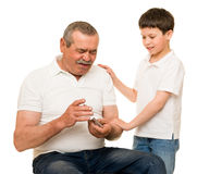 Grandfather and grandchildren playing cards Stock Images