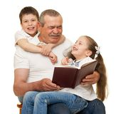 Grandfather and grandchildren read book. On white royalty free stock photos
