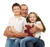 Grandfather and grandchildren read book Stock Photo