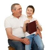 Grandfather and grandchildren read book. On white stock image