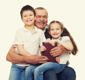 Grandfather and grandchildren read book Stock Images
