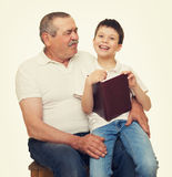 Grandfather and grandchildren read book Royalty Free Stock Photos