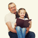Grandfather and grandchildren read book Stock Photography