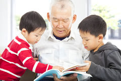 Grandfather and grandchildren reading a book. At home stock photography