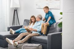Grandfather and grandchildren reading book. While sitting on sofa at home stock photo