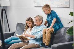 Grandfather and grandchildren reading book. While sitting on sofa at home royalty free stock photo