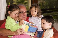 Grandfather and grandchildren reading together. Caucasian grandfather and grandchildren reading together Royalty Free Stock Photos