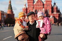 Grandfather with grandchildren on red square Stock Photo