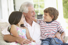 Grandfather And Grandchildren Relaxing In Chair Stock Image