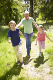 Grandfather With Grandchildren Running Through Countryside Stock Image