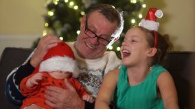 Grandfather With Grandchildren Sits On Sofa At Christmas. Sister puts a baby on a Santa hat. Baby surprised
