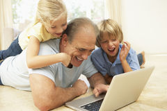 Grandfather And Grandchildren Using Laptop At Home Stock Image