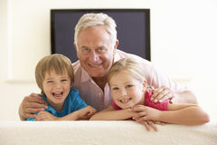 Grandfather And Grandchildren Watching Widescreen TV At Home Stock Images