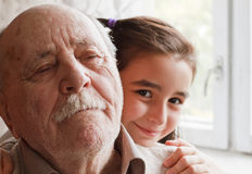 Grandfather and granddaughter. Little granddaughter loving her grandfather royalty free stock image