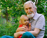 Grandfather and granddaughter. The grandfather sits on a lawn and holds the cheerful grand daughter on hands Royalty Free Stock Photography
