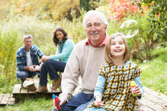 Grandfather And Granddaughter Blowing Bubbles Royalty Free Stock Images