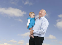 Grandfather and granddaughter, blue sky with clouds Stock Photo