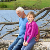 Grandfather and granddaughter. Cheerful and funny grandfather and granddaughter hugging in nature Stock Photography