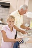 Grandfather And Granddaughter Cleaning Dishes Royalty Free Stock Image