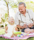 Grandfather and Granddaughter Coloring Easter Eggs on Blanket At Stock Photography