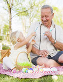 Grandfather and Granddaughter Coloring Easter Eggs on Blanket At Stock Photos
