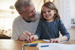 Grandfather And Granddaughter Colouring Picture Together stock image