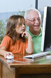 Grandfather and granddaughter with computer. At home Royalty Free Stock Photo