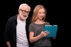 Grandfather and granddaughter with digital tablet. Smiling grandfather and granddaughter using digital tablet isolated on black Royalty Free Stock Images
