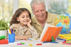 Grandfather with granddaughter drawing together Stock Photo