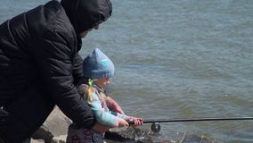 Grandfather Helps Granddaughter Fishing. Grandfather and Granddaughter are Fishing in Spring Sunny Day. Elderly Man Helping Young Girl to Cast a Fishing Pole in stock video