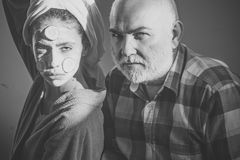 Grandfather and granddaughter. Girl and old man with beard and bold forehead Stock Image