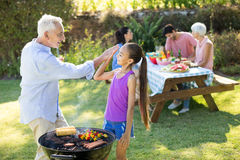 Grandfather and granddaughter giving a high five while preparing barbecue Stock Photo