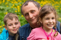 Grandfather, granddaughter and grandson smiling Royalty Free Stock Image