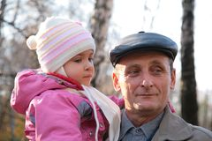 Grandfather with  granddaughter on hands Royalty Free Stock Photos