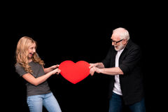 Grandfather and granddaughter with heart symbol. Happy grandfather and granddaughter holding red heart symbol isolated on black Stock Photos