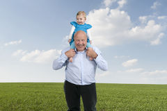 Grandfather with granddaughter on his shoulders, walking in mead Royalty Free Stock Photo