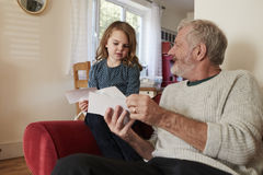 Grandfather And Granddaughter At Home Looking At Photographs Royalty Free Stock Photos