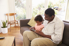 Grandfather And Granddaughter At Home Using Digital Tablet Royalty Free Stock Image