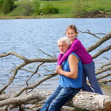 Grandfather and granddaughter hugging in nature. Cheerful and funny grandfather and granddaughter hugging in nature Stock Images