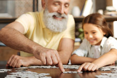 Grandfather and granddaughter joining two jigsaw puzzle pieces. Effective cooperation. Charming elderly men and his lovely little granddaughter sitting at the Royalty Free Stock Photos