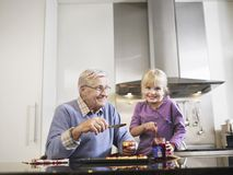Grandfather And Granddaughter In Kitchen Royalty Free Stock Images