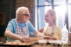 Grandfather and granddaughter kneading dough Stock Photography