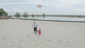 Grandfather and granddaughter launch a kite on the beach at the lake. Filming from the air. 4K Slow Mo. Grandfather and granddaughter launch a kite on the beach stock video