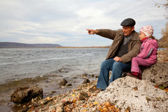 Grandfather and granddaughter look at lake Royalty Free Stock Photo