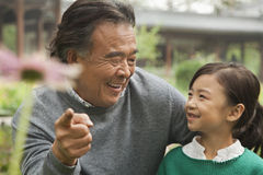Grandfather and granddaughter looking at flower in garden royalty free stock photos