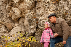 Grandfather and granddaughter near stone wall Royalty Free Stock Images