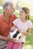 Grandfather and granddaughter outdoors with ball Royalty Free Stock Image