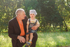 Grandfather and Granddaughter Outdoors Smiling Stock Image