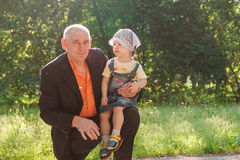 Grandfather and Granddaughter Outdoors Smiling Stock Photo